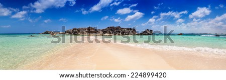 Dragon Cay at low tide with the sandy causeway and rocks mostly exposed, Mudjin Harbor, Middle Caicos - stock photo