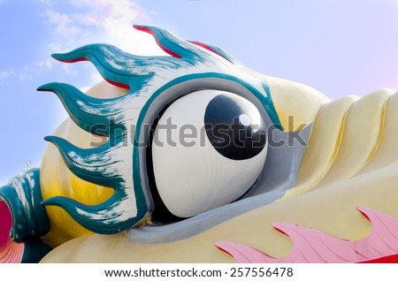 Dragon eye with blue sky. - stock photo