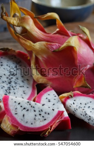 Dragon fruit - pitaya whole fruit and slices, close up vertical