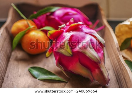 Dragon fruits and tangerines on a wooden tray  - stock photo
