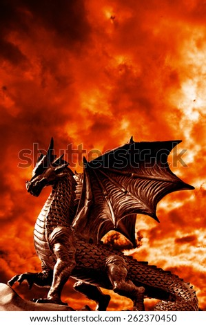 dragon in front of a dramatic red sky - stock photo