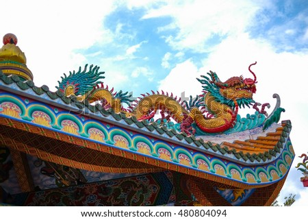 Dragon sculpture on the roof of a Chinese temple .