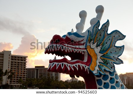 Dragon shaped head on traditional canoe on sand in Waikiki with hotels - stock photo