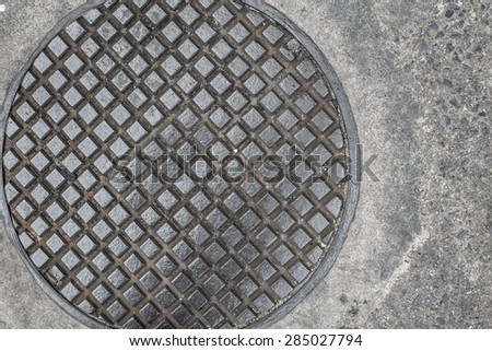 Drain cap on the concrete of sewer cover on the walk way old strong steel iron and grungy. - stock photo