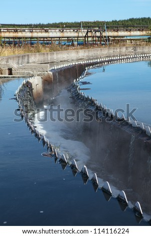 Drainage in sedimentation reservoir with clean water overflowing - stock photo