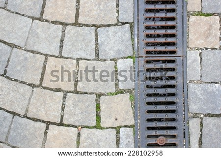 drainage on pedestrian street, textured background  - stock photo