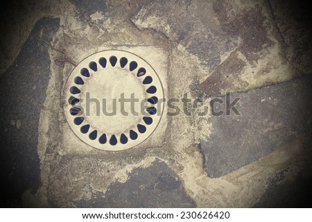 drainage on stone paved street with vignette, vintage style - stock photo