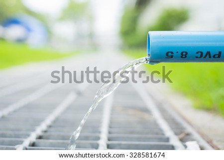 drainage water from pvc pipe (shallow DOF) - stock photo