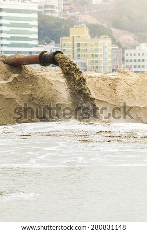 Draining mud water with city building on background. - stock photo