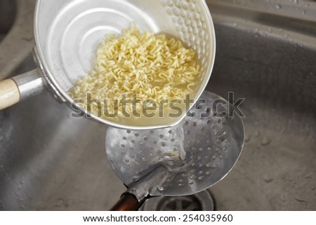 Draining the boiled instant noodle using sieve - stock photo