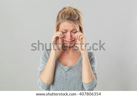 drama concept - complaining young blond woman crying with big tears expressing sadness and disappointment, grey background studio - stock photo