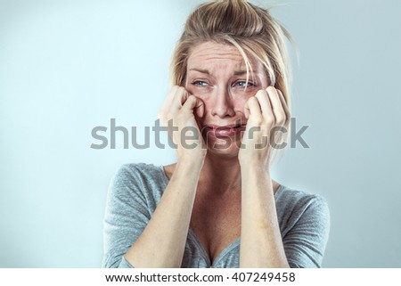 drama concept - disillusioned young blond woman crying with big tears expressing her disappointment and sadness, grey background studio, contrast effects - stock photo