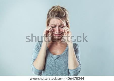 drama concept - gloomy young blond woman crying with big tears expressing failure and disappointment, grey background studio, contrast effects - stock photo