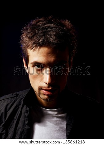 Drama portrait of a handsome guy over black background