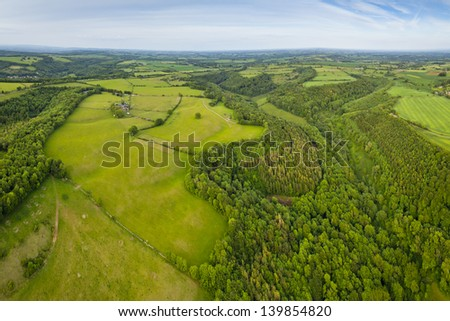 Dramatic aerial view of idyllic rolling patchwork farmland with pretty wooded boundaries, lit in warm early evening sunshine in the heart of the Cotswolds, England, UK. - stock photo