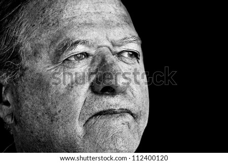 Dramatic and powerful black and white portrait of a senior man with pale eyes looking away great facial details, perfect for aging or other old age issues. - stock photo