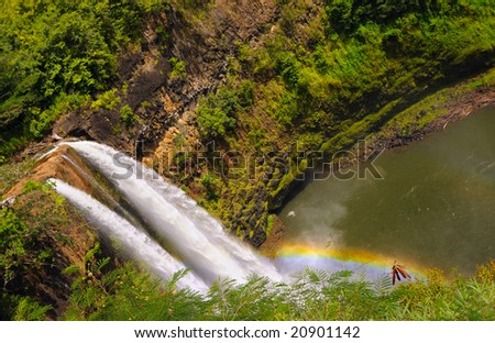 Dramatic angled view of Wailua Falls with rainbow on the island of Kauai