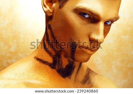 Dramatic art portrait of man in bronze paint on his body and gold makeup.  Close up portrait of a man with the trace from women's hands - stock photo
