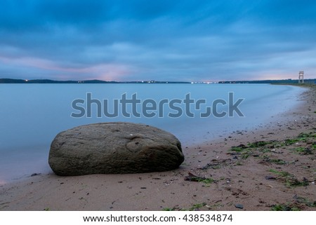 Dramatic atmosphere in peaceful evening at sea. Big boulder sticking out from smooth wavy sea. Blue horizon with cold rain clouds. Stormy sea. Long exposure. One big rock on the corner