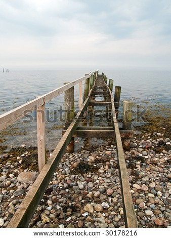 Dramatic beautiful seascape with an old wooden footbridge - stock photo