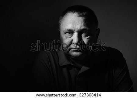 Dramatic black and white close up portrait of aged man sitting and looking at camera against wall - depression concept - stock photo
