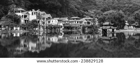 Dramatic Black and White Landscape of Village Near Hanoi Vietnam Pagoda on Lake with Reflections - stock photo