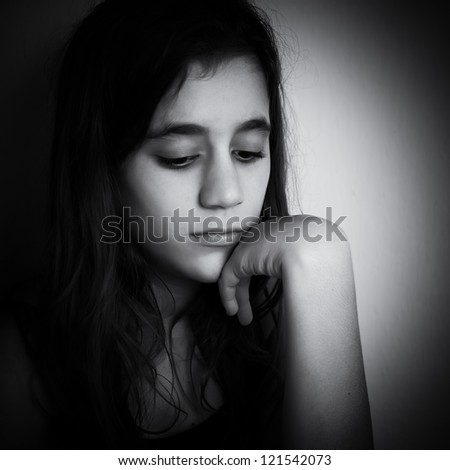 Dramatic black and white portrait of a sad and lonely child