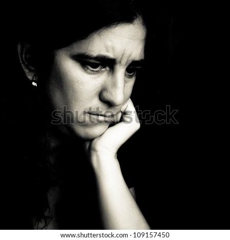 Dramatic black and white portrait of a worried young woman on a black background