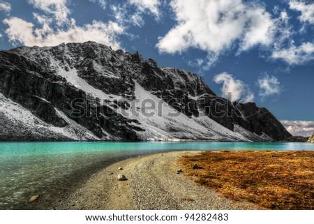 Dramatic black cliff over sandy mountain lake shore - stock photo