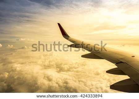 Dramatic blue sky with a big cloud coating with orange sunset light and wing of the airplane - stock photo