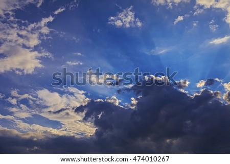 Dramatic blue sky with sun rays and clouds