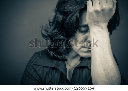 Dramatic  blue toned portrait of a woman suffering a headache or a strong depression - stock photo