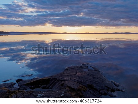Dramatic clouds and vibrant colors of sunset at a lake in Finland one calm spring evening. The sun is just behind the clouds ready to appear. - stock photo