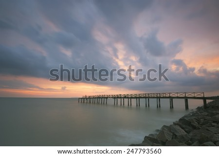 Dramatic clouds at sunset over the wooden bridge  (soft focus, shallow DOF, slight motion blur)  - stock photo
