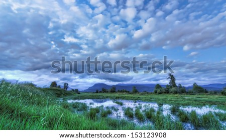 Dramatic clouds mountain and water in this blue landscape - stock photo