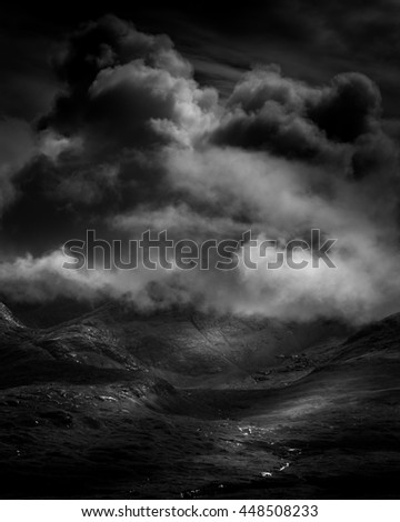 Dramatic clouds over mountain landscape with rocks and rough terrain and interesting lighting and shadows