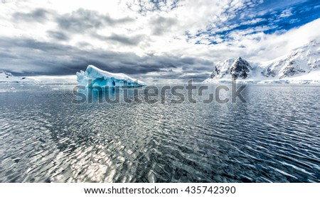 Dramatic clouds over mountains and icebergs near Neko Bay in Antarctica - stock photo