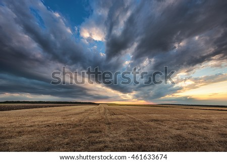 Dramatic clouds over the field after harvest, sunset shot