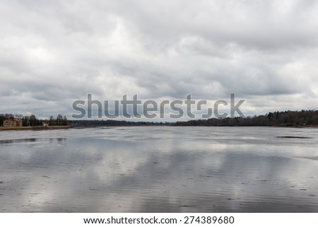 dramatic clouds over the river in misty morning in spring with reflections in water