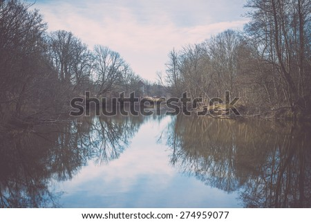 dramatic clouds over the river in misty morning in spring with reflections in water - retro vintage looking effect