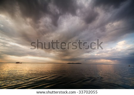 dramatic clouds over the sea on sunset - stock photo