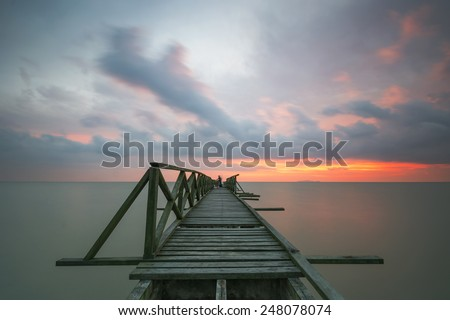 Dramatic clouds over the wooden broken bridge at the beach  (soft focus, shallow DOF, slight motion blur)  - stock photo