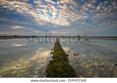 Dramatic clouds reflection over water reservoir at morning. Soft focus due to long exposure shot. Composition of nature.  - stock photo