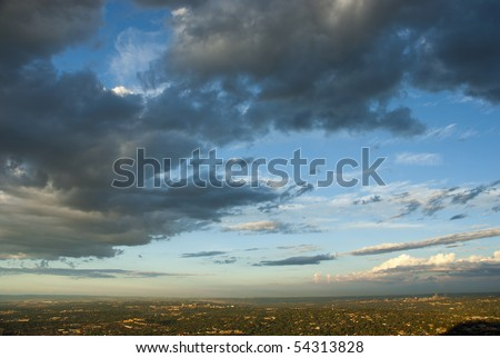 Dramatic clouds with blue skies over the Johannesburg city skyline, just before sunset - stock photo
