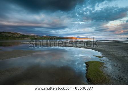 Dramatic Cloudscape and distant sunbeam at Lake Laberge, Yukon Territory, Canada - stock photo