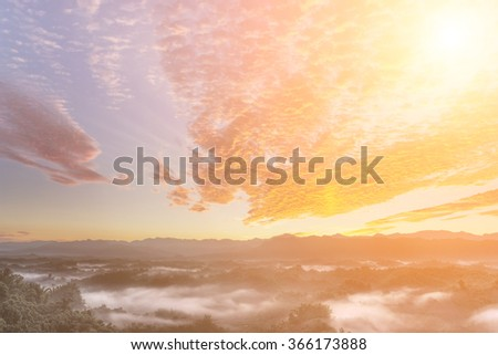 Dramatic cloudscape in morning with red clouds on sky and green mountain in countryside. - stock photo