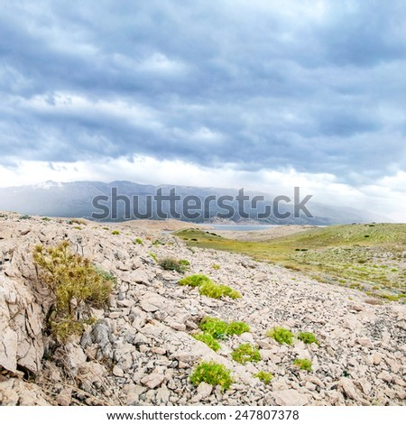 Dramatic cloudscape on stone desert with see afar - stock photo