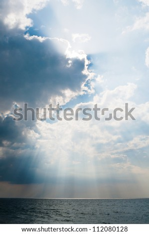 Dramatic cloudy sky after a storm and rain under sea surf - stock photo