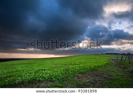 Dramatic cloudy sky over countryside landscape with vibrant colors - stock photo