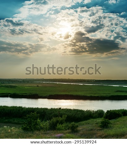 dramatic cloudy sky over river in green canes - stock photo